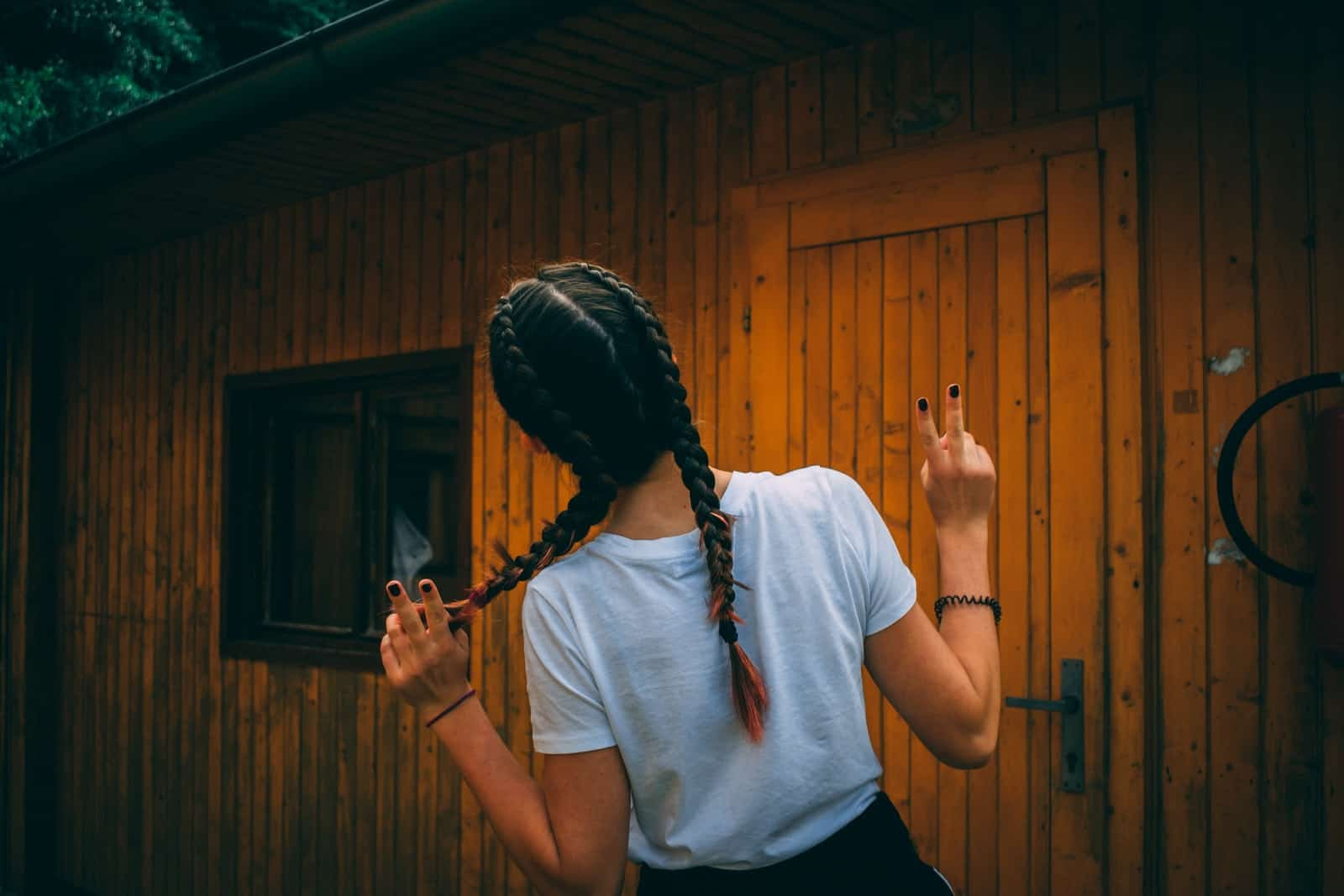 Woman with braided hair outside wooden shack / shed