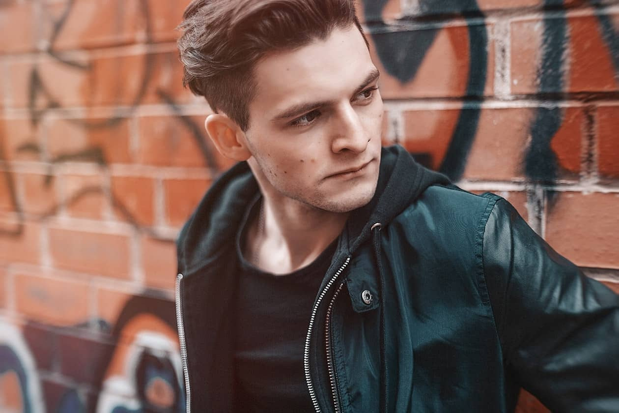Man leaning against wall with mid length fade hair cut